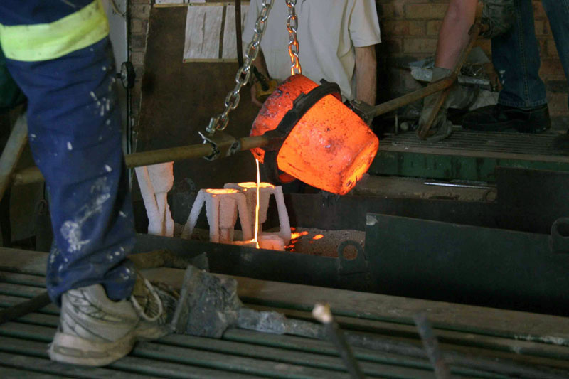 Pouring molten bronze into the ceramic moulds